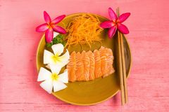 Salmon sashimi on dish with flower on wood color pink.  royalty free stock photography