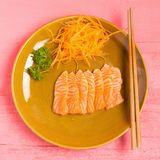 Salmon sashimi on dish on wood color pink.  royalty free stock images