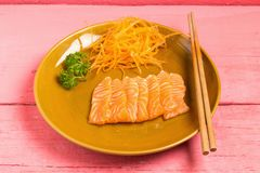 Salmon sashimi on dish on wood color pink.  royalty free stock image
