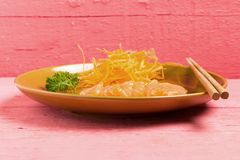 Salmon sashimi on dish on wood color pink.  royalty free stock photography