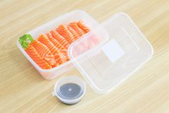 Salmon Sashimi inside a plastic box container ready to serve meal with soy sauce in a plastic cup container. The ready to go salmo. N sashimi chunck good with Royalty Free Stock Photo