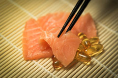 Salmon Sashimi mixed with  Fish oil capsules with chopstick grab Stock Image