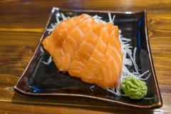 Salmon Sashimi op een zwarte Ceramische Plaat met Gedeelte van Wasabi Stock Foto