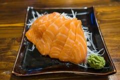 Salmon Sashimi op een zwarte Ceramische Plaat met Gedeelte van Wasabi Royalty-vrije Stock Foto's