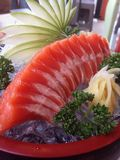 Salmon sashimi. On red plate with garnish Royalty Free Stock Images