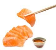 Salmon sashimi set. Isolated salmon sashimi set with chopsticks holding a piece of sliced salmon royalty free stock images