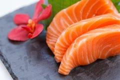 Salmon Sashimi: Skivade rå Salmon Served med den skivade rädisan på stenplattan arkivbild