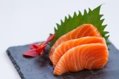Salmon Sashimi: Skivade rå Salmon Served med den skivade rädisan på stenplattan fotografering för bildbyråer
