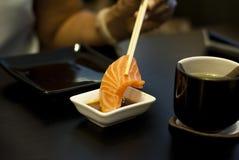 Salmon Sashimi tauchte in Sojasoße ein Stockfotografie