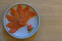 Salmon sashimi with white plate on wood background. stock image