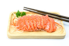 Salmon sashimi on a wooden plate. With wooden chopsticks isolated on white background Stock Image