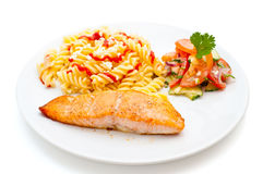 Salmon served with pasta and salad Royalty Free Stock Images