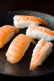 Salmon and Shrimp Sushi. Laid neatly on dark colored plate Royalty Free Stock Photography