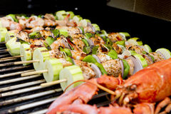 Salmon Skewers and Lobster BBQ. Salmon and Vegetable Skewers and Lobster are on the barbecue Stock Photo