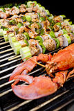 Salmon Skewers and Lobster BBQ. Salmon Skewers and Lobster are on the barbecue Royalty Free Stock Photos