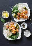 Salmon skewers, olives, spinach, rice - healthy lunch table. Grilled salmon fish skewer and side dish on a dark background royalty free stock image