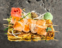 Salmon skewers on vegetable omelette. Over concrete background Stock Photo