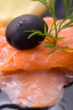 Salmon slice, close up. Salmon with lemon slices, dill and black olive. Close up Stock Images