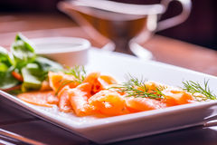Salmon. Sliced smoked salmon with dressing and herb decoration.Serving sliced salmon in a restaurant or hotel Stock Images