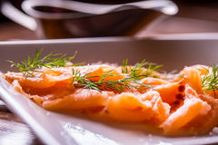 Salmon. Sliced smoked salmon with dressing and herb decoration.Serving sliced salmon in a restaurant or hotel Royalty Free Stock Photos