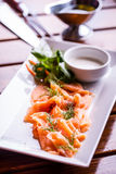 Salmon. Sliced smoked salmon with dressing and herb decoration.Serving sliced salmon in a restaurant or hotel Stock Image