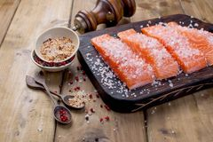 Salmon is sliced and sprinkled with salt and spices, on a wooden table. Free space for text. Seafood. Healthy food. copy space stock image