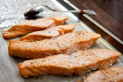 Salmon slices fried in a frying pan in sauce.  Stock Images