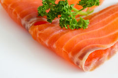Salmon slices with parsley on white. Close up Royalty Free Stock Images