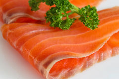 Salmon slices with parsley on white. Close up Stock Images