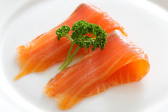 Salmon slices with parsley on a white plate. Close up Royalty Free Stock Photo