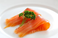 Salmon slices with parsley on a white plate. Close up Stock Photo