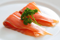 Salmon slices with parsley on a white plate. Close up Stock Photos