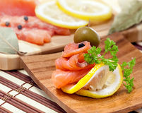 Salmon snack. With lemon and parsley on a wooden plate, studio shot Royalty Free Stock Photography