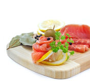 Salmon snack on a wooden board. Isolated on white, studio shot Stock Images