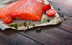 Salmon slice on a wooden table. Salmon with some ingredients on a wooden textured table of a home cuisine. Healthy food concept Stock Images