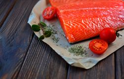 Salmon with some ingredients on a wooden textured table. Of a home cuisine royalty free stock photography