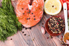 Salmon with spices and lemon on wooden table.  Royalty Free Stock Photo