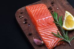 salmon and spices on a wooden cutting board stock image