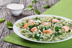 Salmon and Spinach Fettuccine pasta on white dish Royalty Free Stock Photo