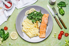 Salmon with Spinach and mashed potatoes , serve on rustic table with seasoning, fork and knife Stock Photo