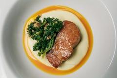 Salmon Steak al forno con la fetta del limone e degli spinaci Immagini Stock Libere da Diritti