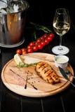 Salmon Steak asado a la parrilla asado Salmones con romero, los tomates de cereza y la salsa cremosa en un tablero de madera imágenes de archivo libres de regalías