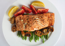 Salmon steak and asparagus from above. Looking down on a plate of pan-fried salmon fillet served on a bed of asparagus with tomatoes and mushrooms royalty free stock photography