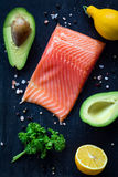 Salmon steak, avocados, lemons, parsley and spices on wooden cutting board Stock Photo