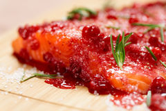 Salmon steak bein marinated in salt with rosemary and redberries Royalty Free Stock Photography