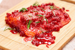 Salmon steak being marinated in salt with redberries Royalty Free Stock Image
