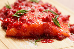 Salmon steak being marinated in salt with redberries Royalty Free Stock Photo