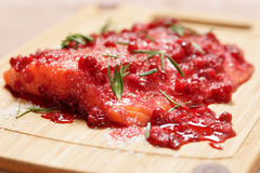 Salmon steak being marinated in salt with redberries Stock Image