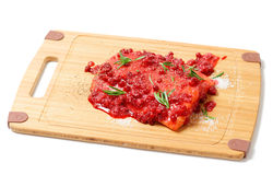 Salmon steak being marinated in salt with rosemary and redberrie Stock Photography