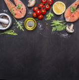 Salmon steak, butter, salt and pepper, lemon and cherry tomatoes on wooden rustic background top view border ,place for text Royalty Free Stock Photography